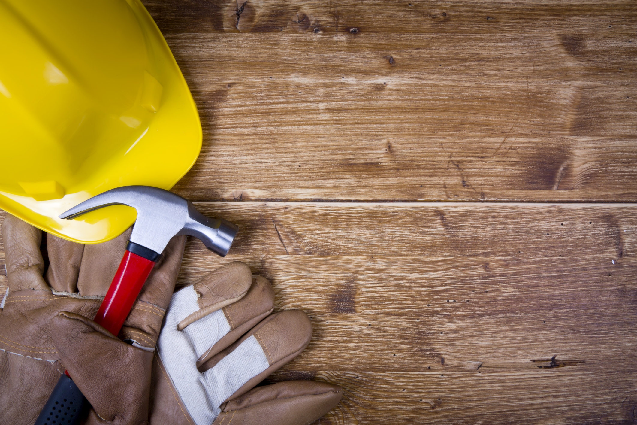 Construction hat, gloves and a hammer on a wood background