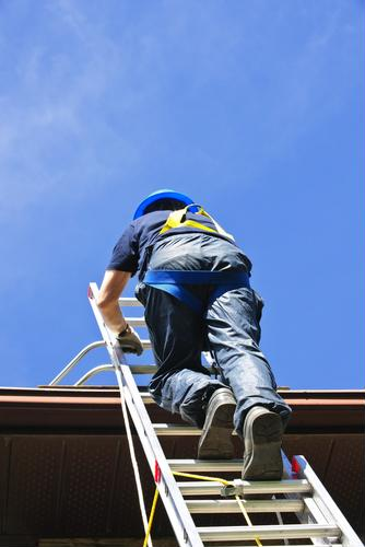 Construction worker climbing a ladder to the roof