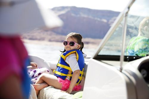 Small girl in sunglasses and a life vest on a boat