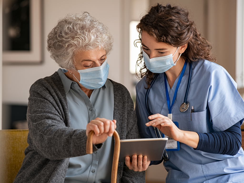 elderly woman and caregiver reading a tablet