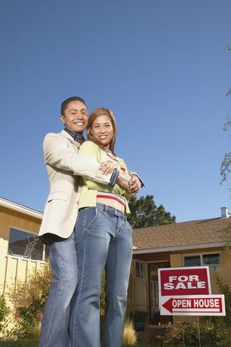 Young couple hugging in front of a for sale sign and open house sign