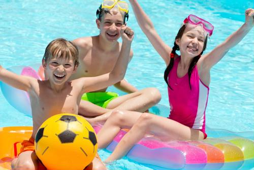 Three smiling kids playing on floating toys in the pool