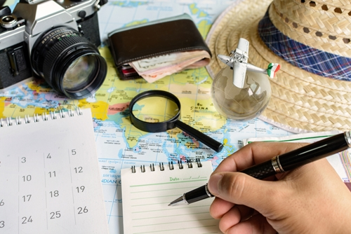 Person holding a pen in front of a hat, calendar and world map
