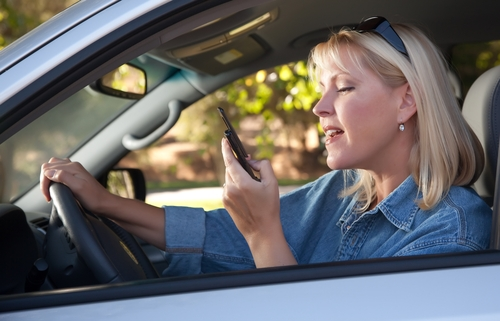 woman looking at her phone while driving