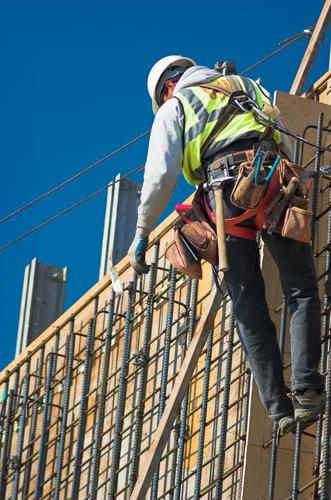 Construction worker on the side of a house in front of rebar