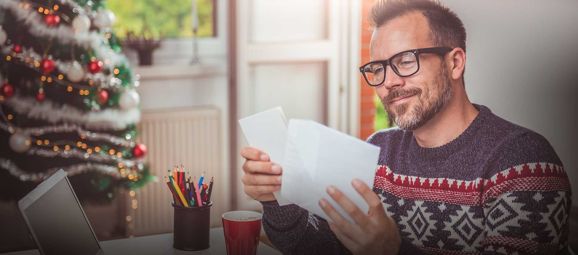 Man in front of Christmas tree stuffing envelopes