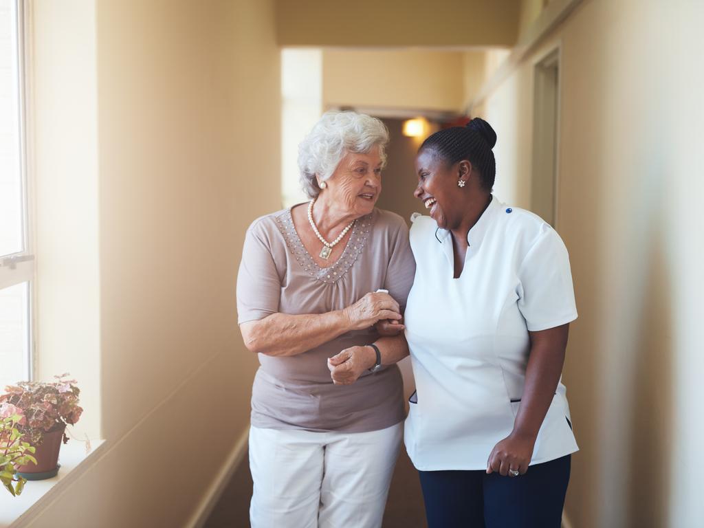 female-caregiver-walking-with-senior-citizen