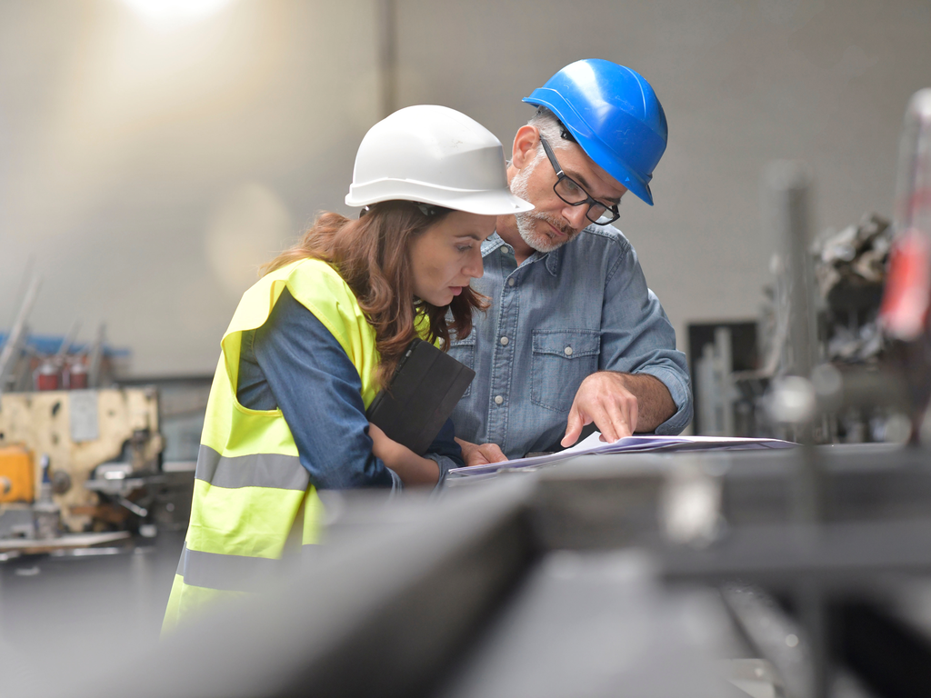 man and woman in hard hats looking at blueprints