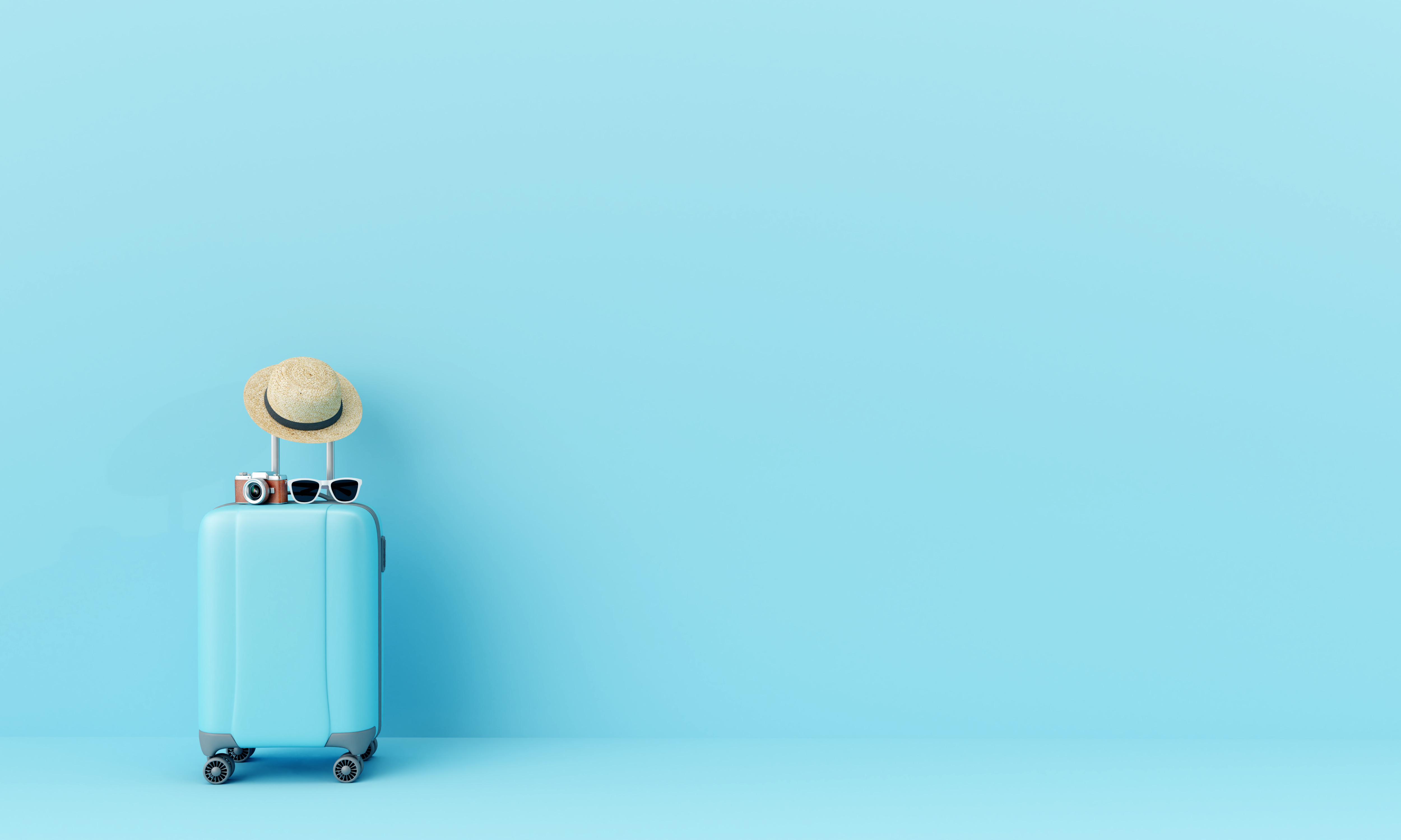 Blue suitcase and hat against a blue background