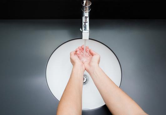 person washing their hands under a sink