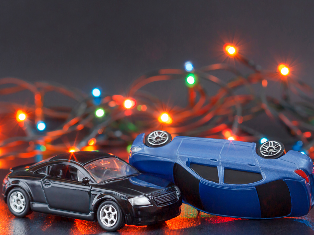 toy cars crashing in front of Christmas lights