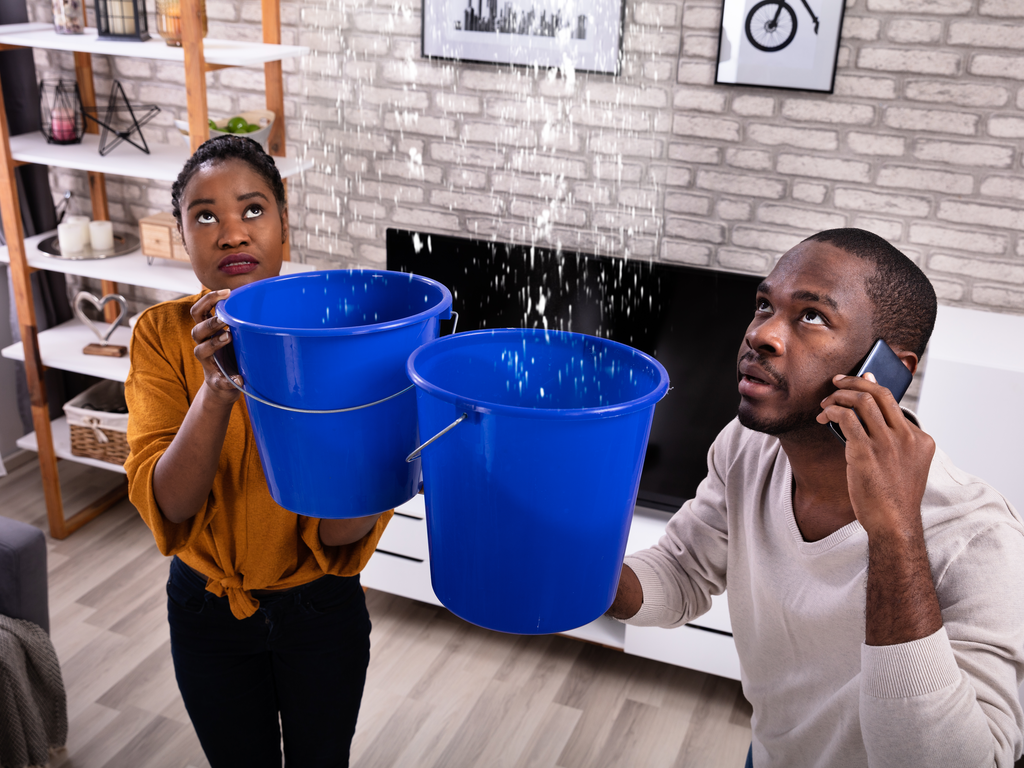 young couple holding buckets under a leaking ceiling
