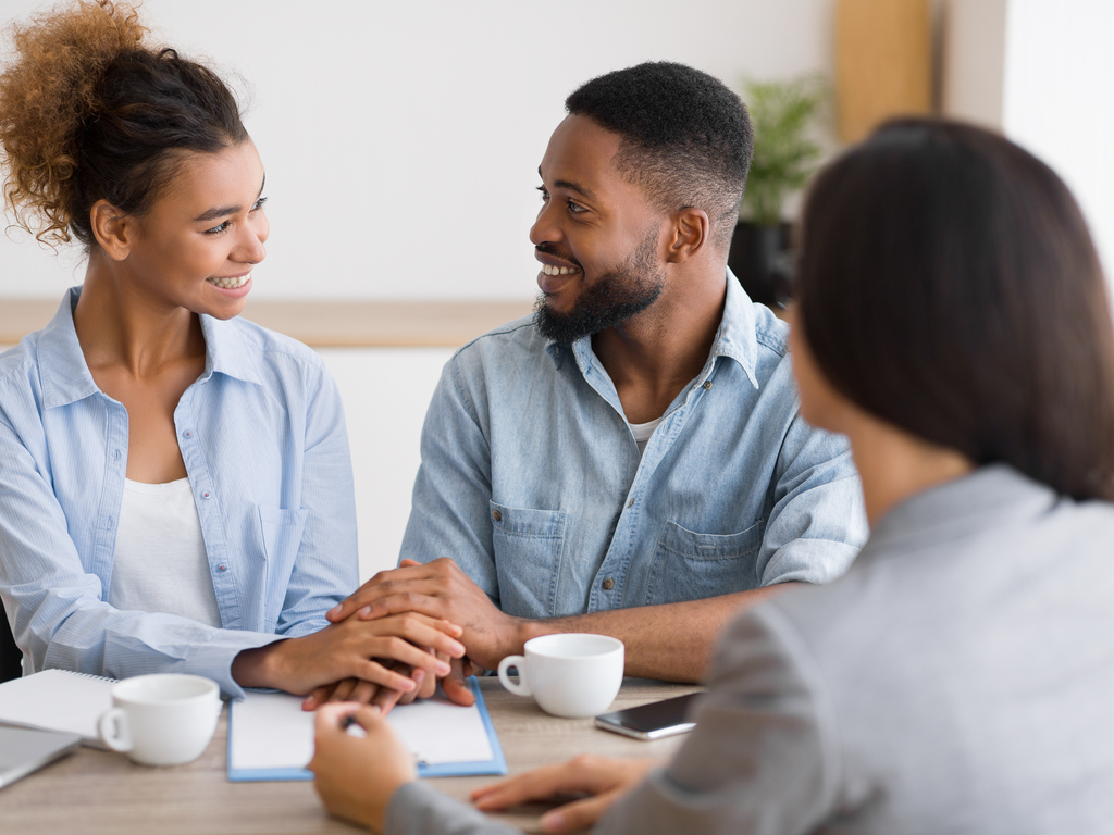 young couple sitting with a financial advisor