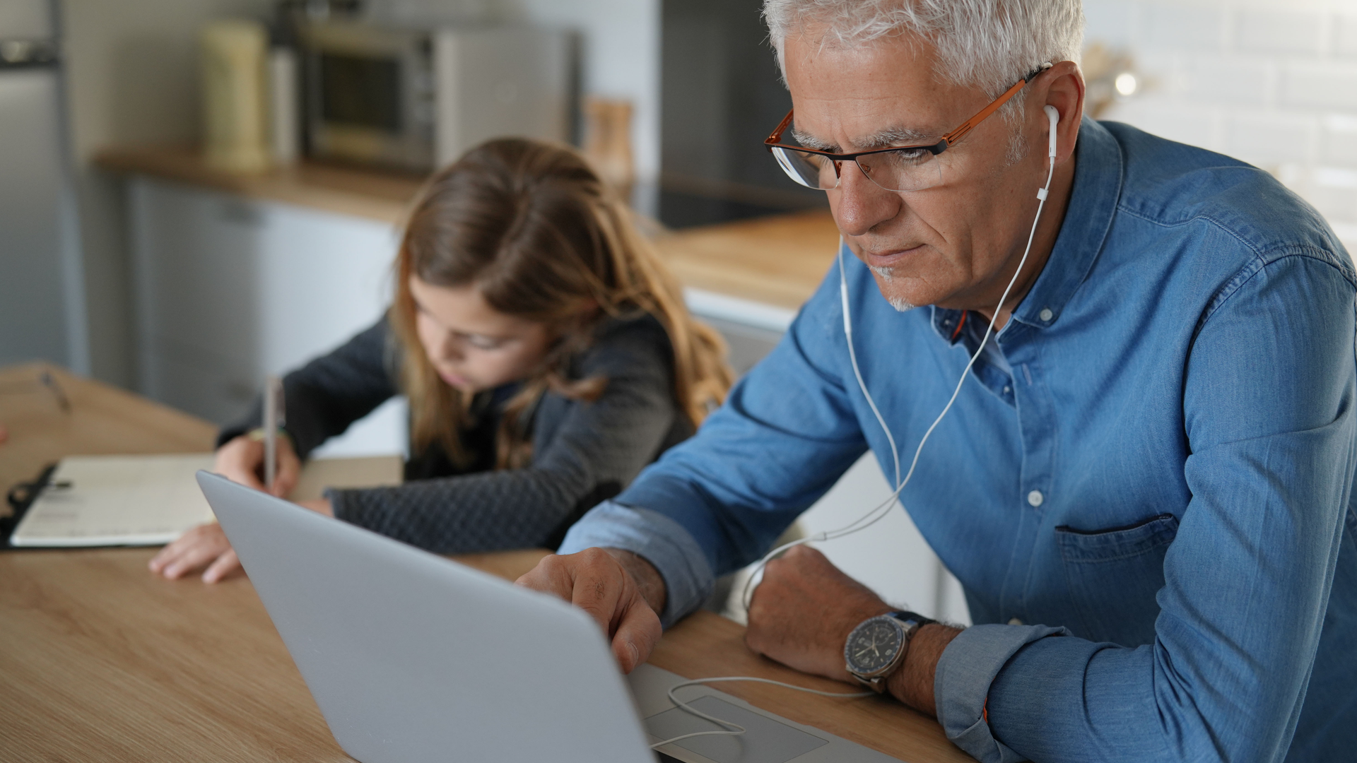 Older man with headphones looking at a computer with a young girl writing in the background