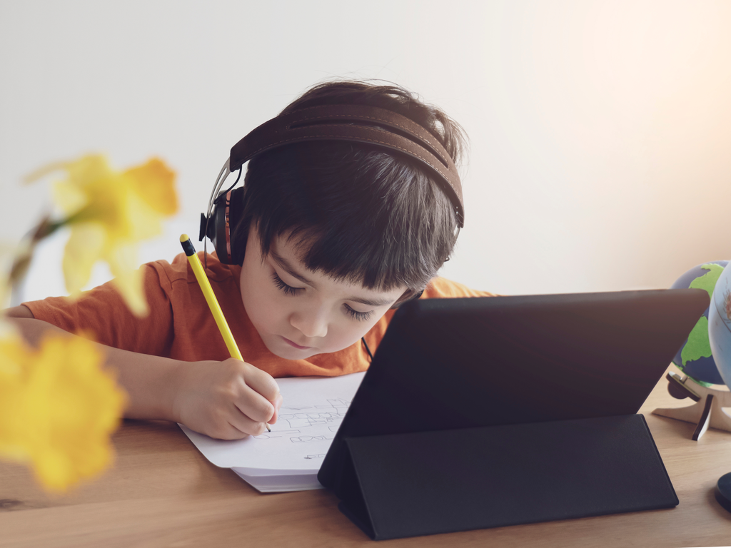 Child with headphones learning in front of a tablet
