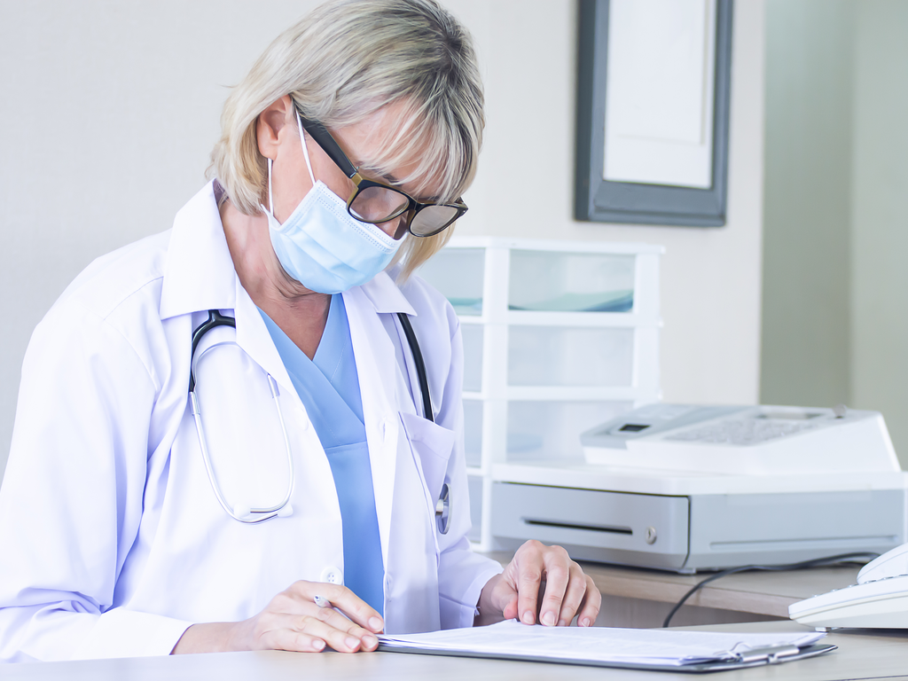 doctor with mask on reviewing forms