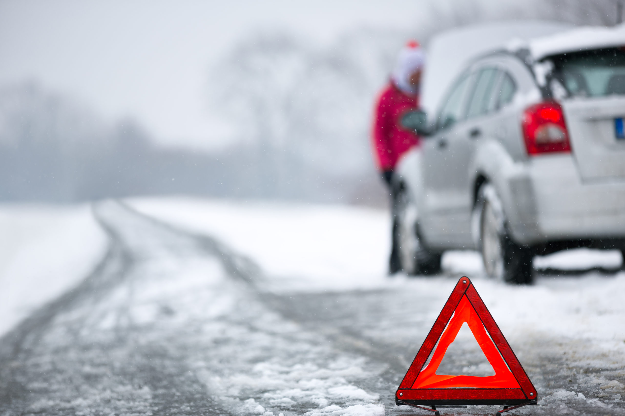 car on the side of a winter road with a warning pylon