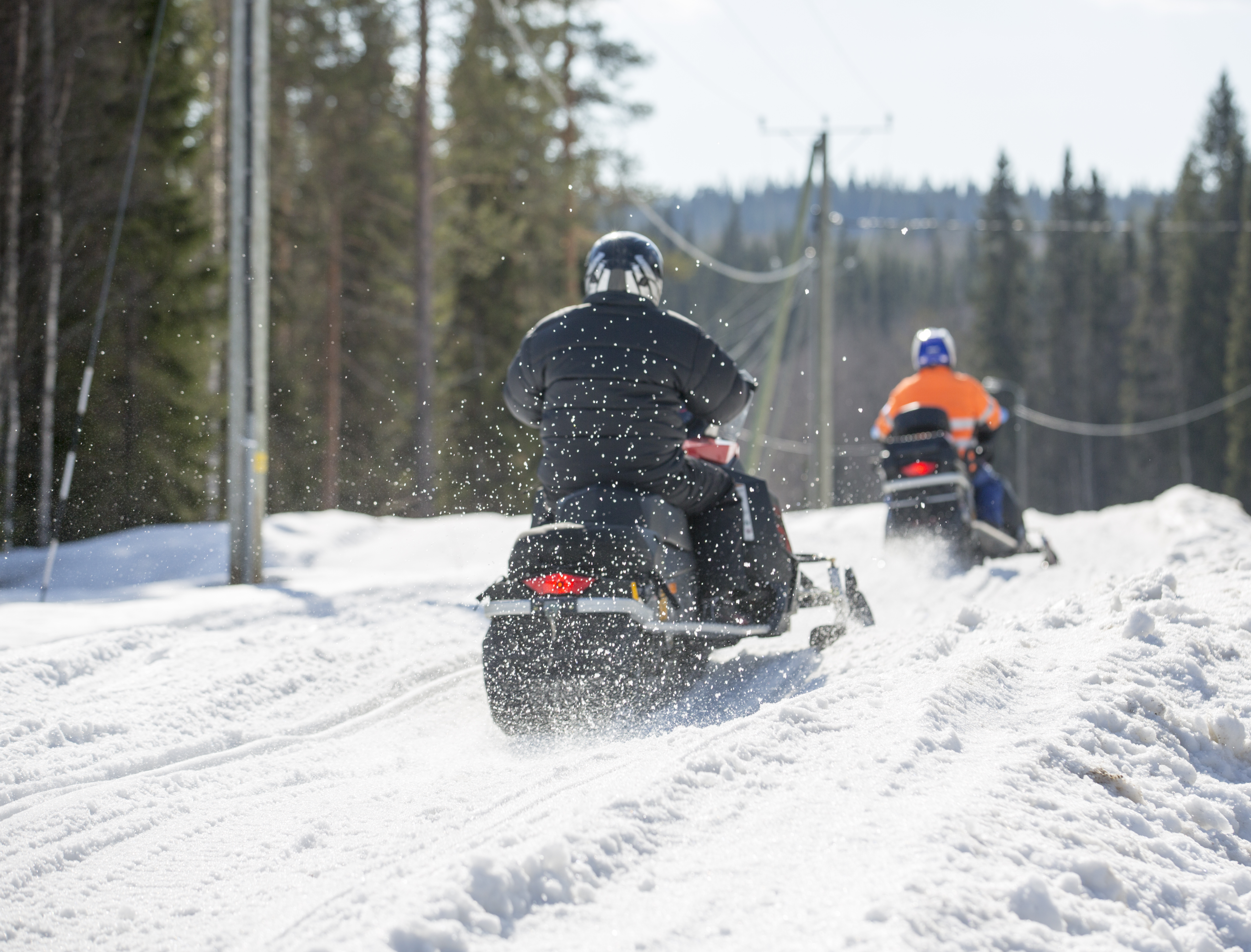 Two people riding snowmobiles in the mountains