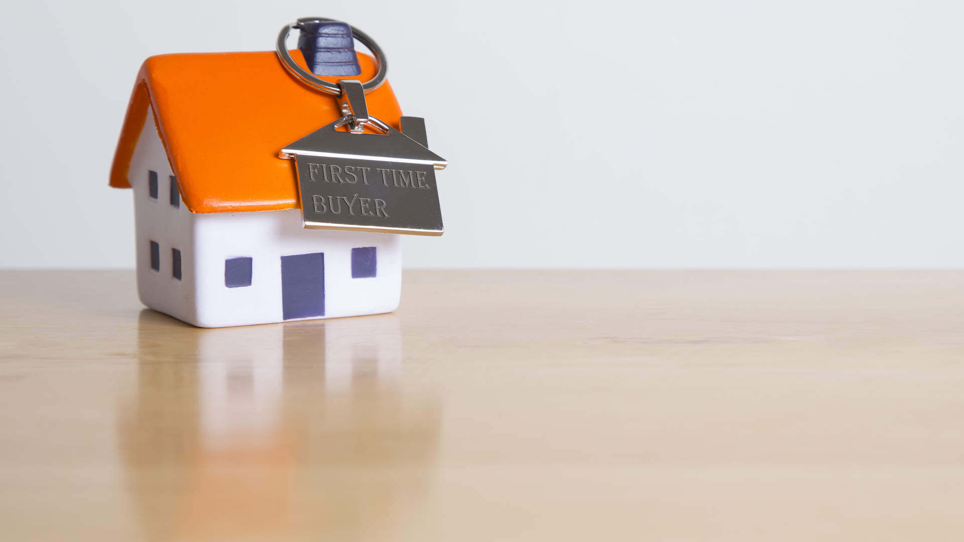 Small house with a keychain that says first time buyer
