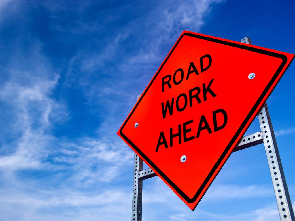 Orange road work ahead sign against a blue sky