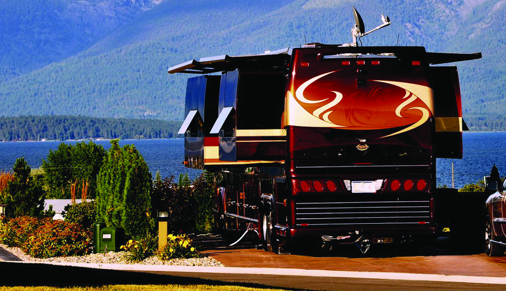 Red RV parked in a camping space next to a lake